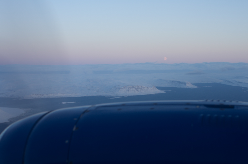 The moon visible above the clouds flying up to Patreksfjordur
